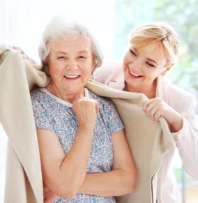 caregiver covering senior woman using towel