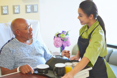 portrait of nurse giving food to senior man
