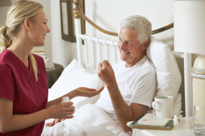 caregiver giving medicine to senior man