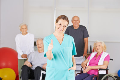 caregiver giving thumbs up while seniors at the back