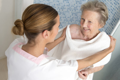 caregiver helping senior woman in bathing