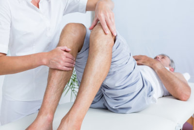 caregiver and senior man having physical therapy